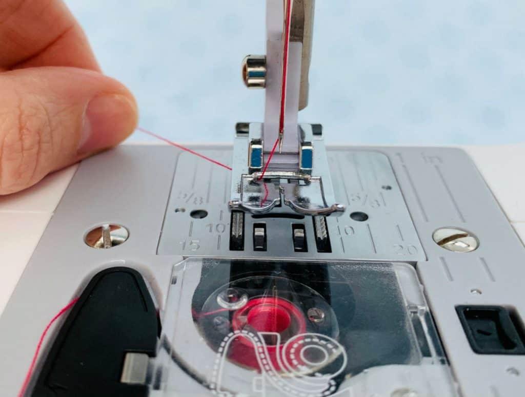 Hold top thread before turning handwheel