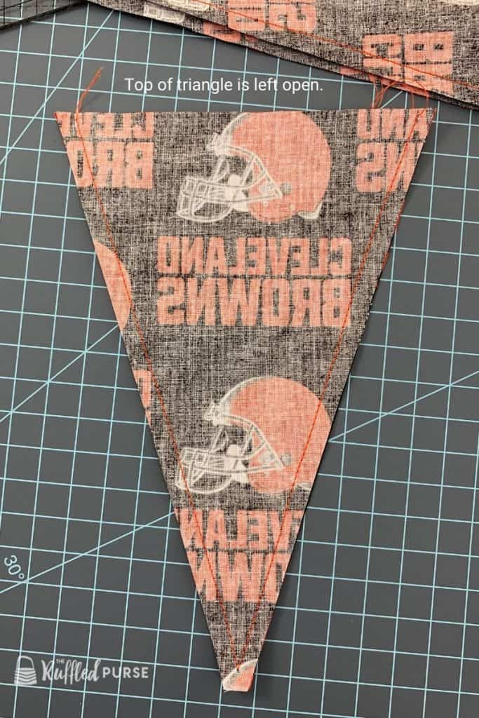 Two sides of pennant are sewn. The top is left open.