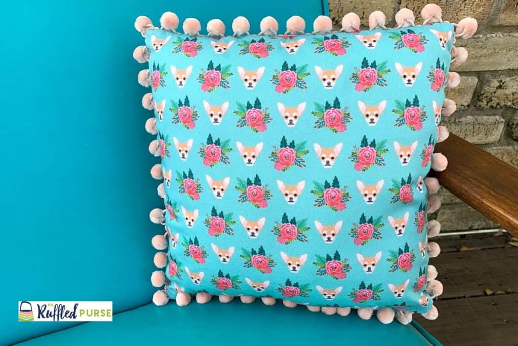 The square pillow cover with pom pom trim on a blue chair.
