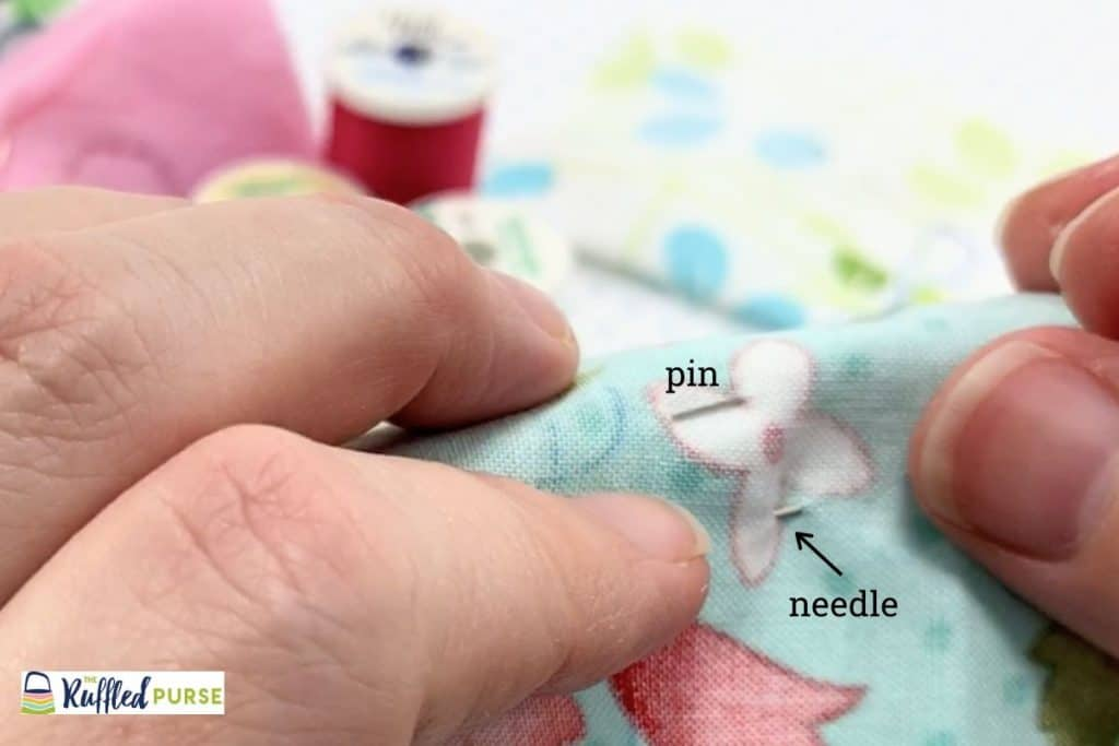 The needle on the back of the under fabric when making a blind stitch.