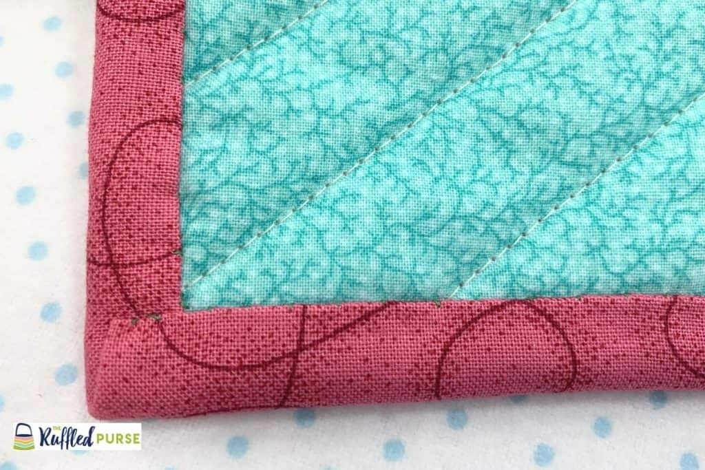 Multiple blind stitches to attach the binding to the back fabric.