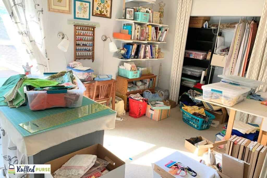 A messy sewing space full of boxes and bins
