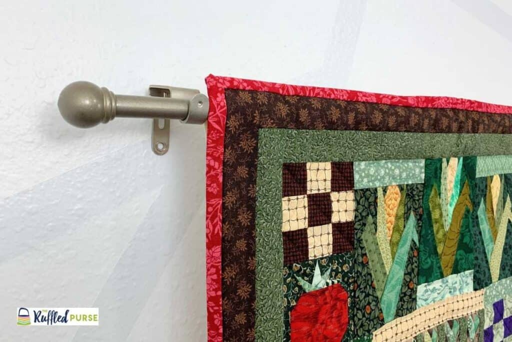 A curtain rod and matching bracket hold this wall hanging in place.