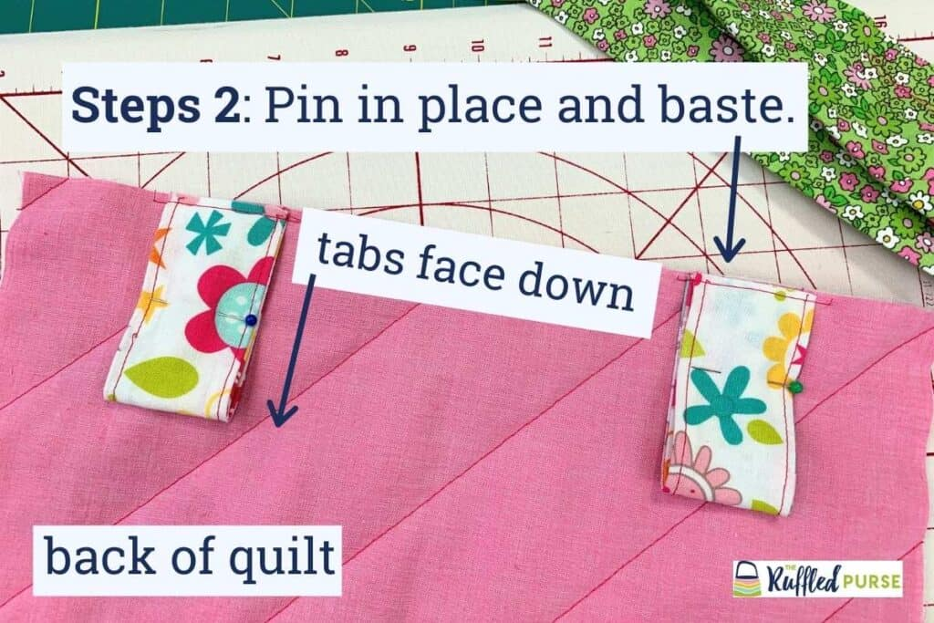Baste the tabs in place on the back of the quilt